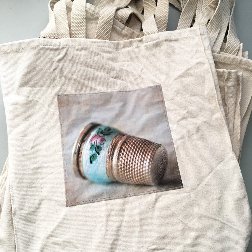 canvas tote bag with image of vintage thimble laying on its side, just above the base the thimble has a blue band with a pink rose and green flowers