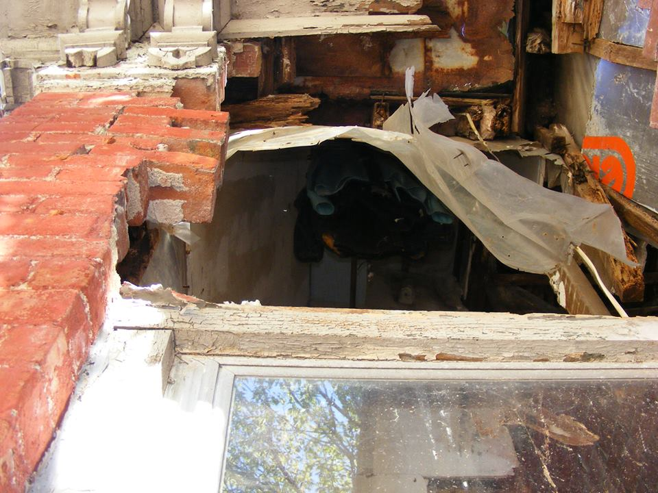 Looking up into the building through a broken wall up to the second floor at clothes hanging on a rod.